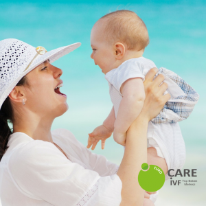 Woman in sunhat holding baby on beach with crystal blue waters in background